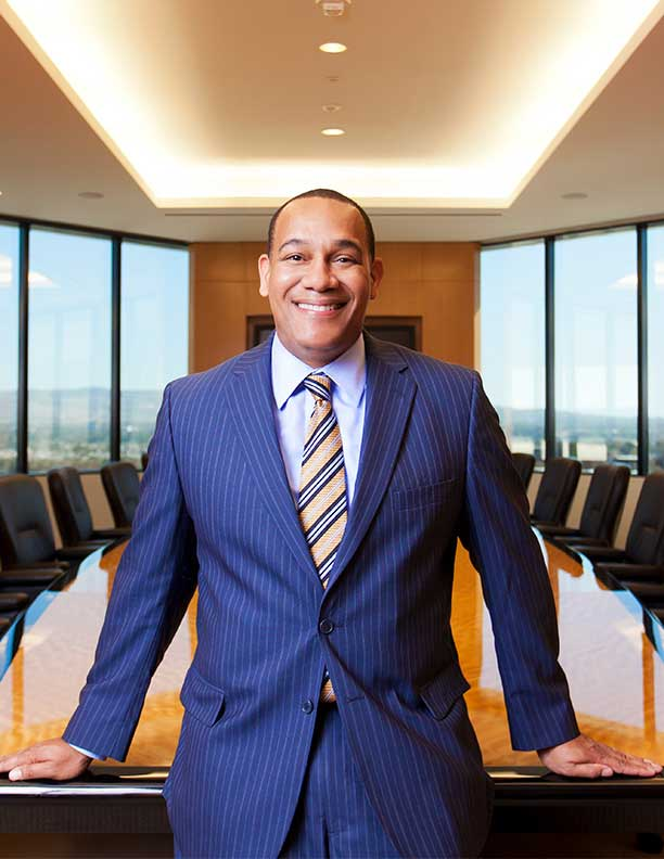portrait of african american ceo smiling in pinstripe suit in front of conference table