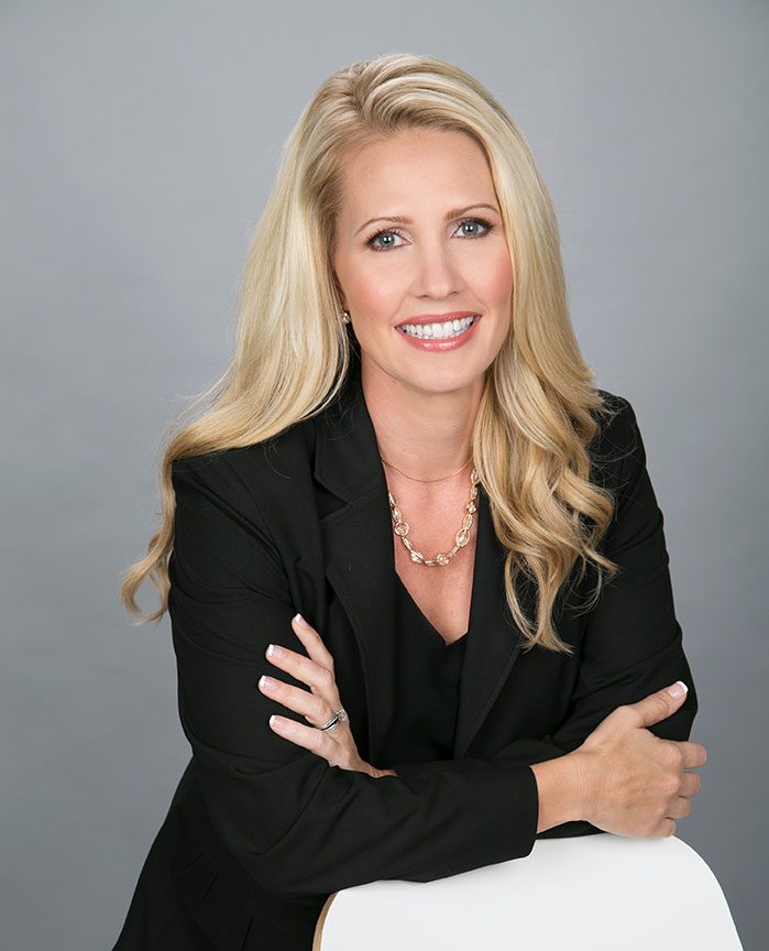 corporate headshot of blond real estate agent woman wearing balc suit smiling with folded arms